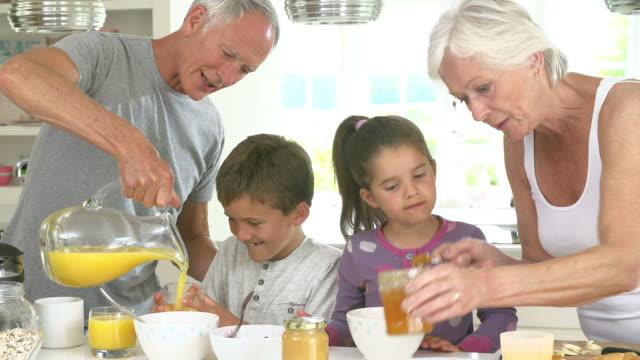 Grandparents With Grandchildren Making Breakfast In Kitchen video