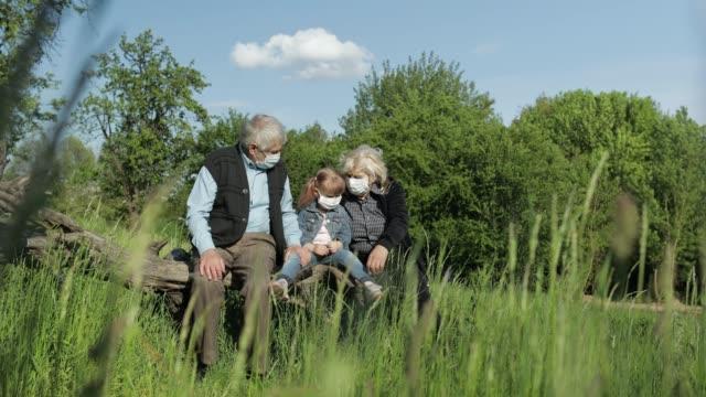 far-och morföräldrar med barnbarn i medicinska masker i parken. coronavirus karantän - helgaktivitet bildbanksvideor och videomaterial från bakom kulisserna