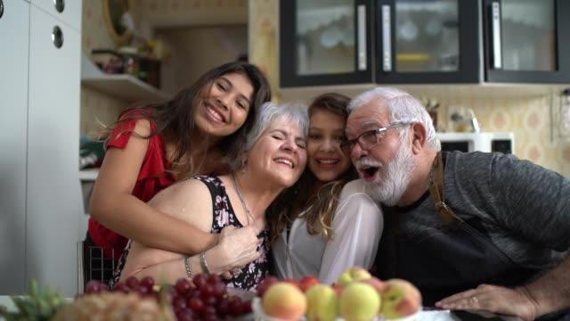 nonni con il nipote in cucina a casa ritratto - pesche bambino video stock e b–roll