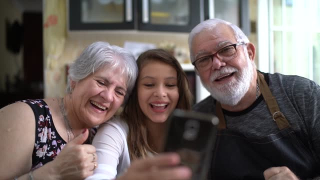 grandparents with their granddaughter having video chat at home - video call with family video stock e b–roll
