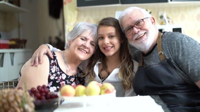 nonni con la nipote in cucina a casa ritratto - pesche bambino video stock e b–roll