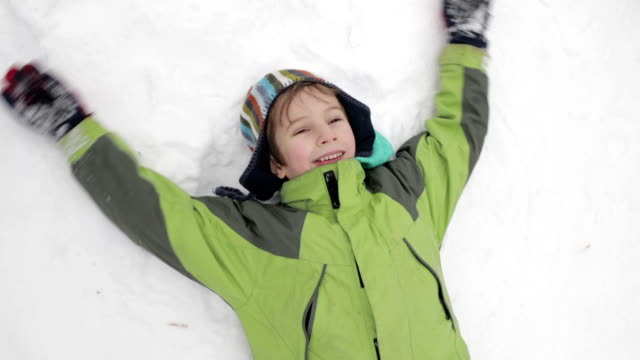 grandson and grandmother making snow angel - кепка стоковые видео и кадры b-roll