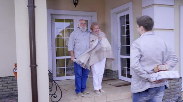 sonson gratulerar morföräldrar med julen och ger dem presenter - christmas gift family bildbanksvideor och videomaterial från bakom kulisserna