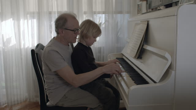 grandson learning how to play the piano. - piano filmów i materiałów b-roll