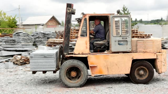 Granite factory. The forklift distributes granite blocks in the warehouse. Factory for the production of granite. construction vehicle stock videos & royalty-free footage