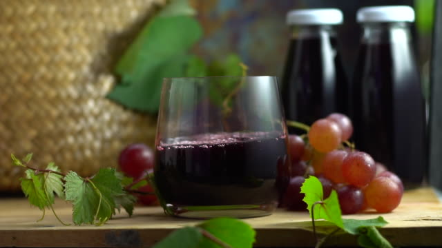 grape juice pouring into crystal glass, organic fresh grapes on background, the best of drink for healthy and holiday celebration ideas concept for advertising, free space for text. - fruit juice bottle isolated video stock e b–roll