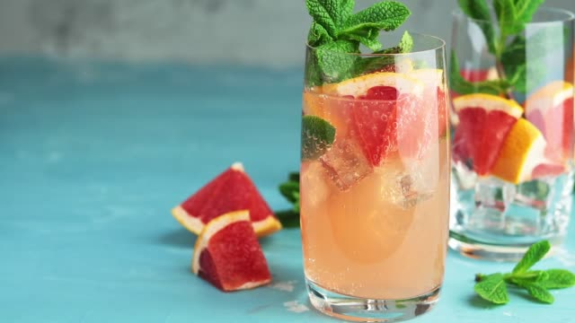 grapefruit and fresh mint cocktail with juice, cold summer citrus refreshing drink gin tonic cocktail or beverage with ice on blue concrete surface. 59.95 fps - rum superalcolico video stock e b–roll
