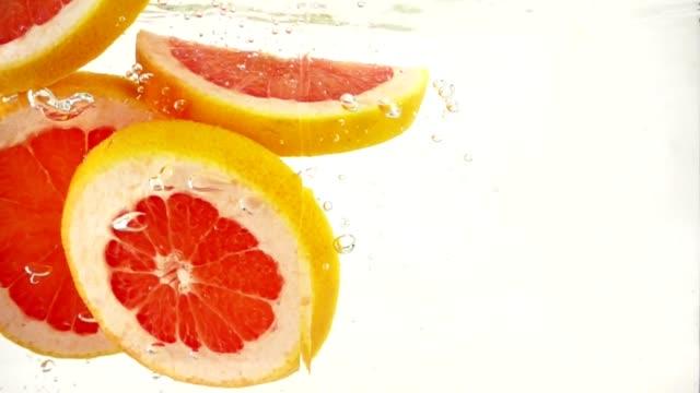 vidéos et rushes de tranches de pamplemousse orange tombent dans l'eau avec jets et bulles, ralenti gros plan - pamplemousse