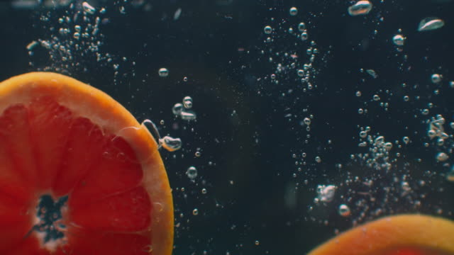 3 Grapefruit rings Underwater with air bubbles and in slow motion. Fresh and juicy healthy vegetarian.