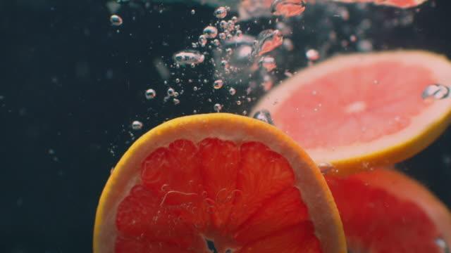 vidéos et rushes de pamplemousse sous l'eau avec des bulles d'air et au ralenti. végétarien sain et juteux et frais. - pamplemousse