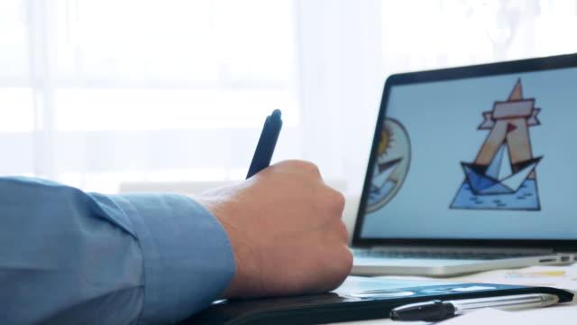 vídeos de stock e filmes b-roll de graphic designer using graphics tablet while working on a logo design - logo
