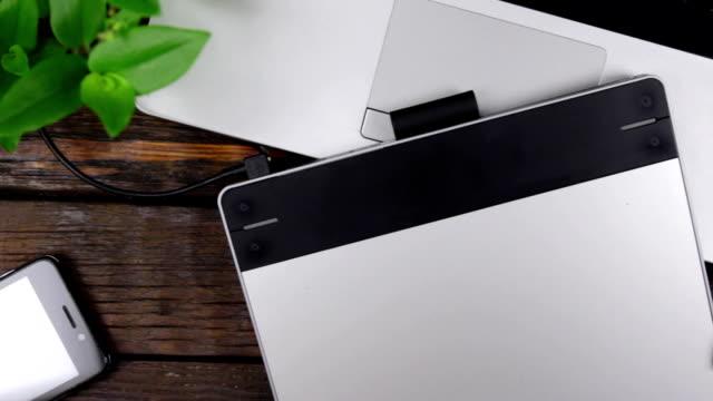 Lieu de travail de concepteur graphique. Tablette graphique et stylet, ordinateur portable et téléphone. Grue de caméra. - Vidéo