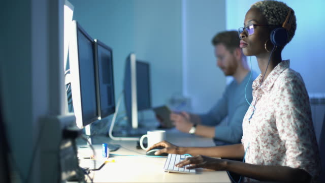 Graphic designers at work. Closeup side view of mid 20's blond black woman doing her design project on a computer. She might be a software developer as well.  She's sitting in front of a desktop computer and sipping a coffee while working on a computer. 4k video. software developer stock videos & royalty-free footage