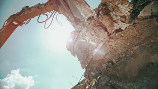 slo mo grapples placing concrete debris onto a pile at the sunny construction site - бетон стоковые видео и кадры b-roll