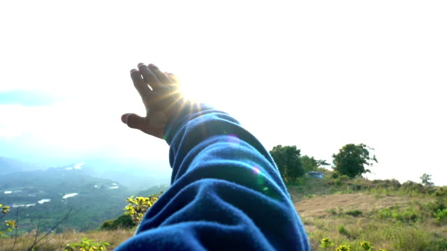 grasping the sun with hand slow motion. male hand against a sun and sky background, grasping the sun and letting sunlight pass through in mountain landscap - armonia video stock e b–roll