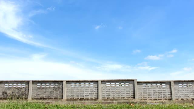 vídeos y material grabado en eventos de stock de hierba pared de ladrillos sky time lapse hd - valla límite