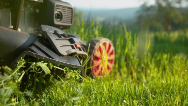 närmör: gräsklipp blir spydda ur en gräsklippare som skjuts runt av trädgårdsmästare. - gräsmatta odlad mark bildbanksvideor och videomaterial från bakom kulisserna