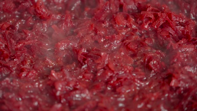 grated beets are fried on a gas stove with an open fire, in a pan in oil. close up, macro. - crucifere brassicali video stock e b–roll