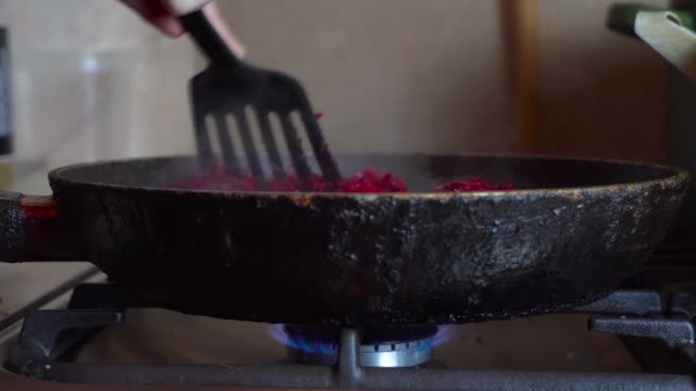 grated beets are fried on a gas stove with an open flame, in a frying pan in oil. - nazionalità russa video stock e b–roll