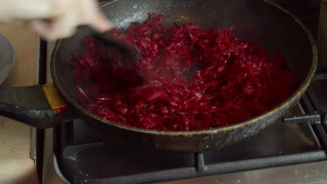 grated beets are fried on a gas stove with an open flame, in a frying pan in oil. - pochodzenia rosyjskiego filmów i materiałów b-roll