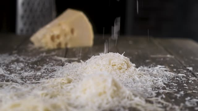 grated cheese pours wooden table. A big pile of grated cheese for pizza grated cheese pours wooden table. A big pile of grated cheese for pizza cheese stock videos & royalty-free footage
