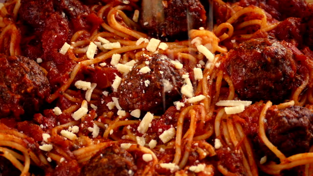 vídeos de stock e filmes b-roll de grated cheese sprinkled on spaghetti and meatballs - sauce