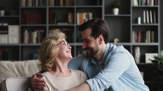dankbar lieben erwachsenen sohn umarmt reife mutter zu hause - dankbarkeit stock-videos und b-roll-filmmaterial