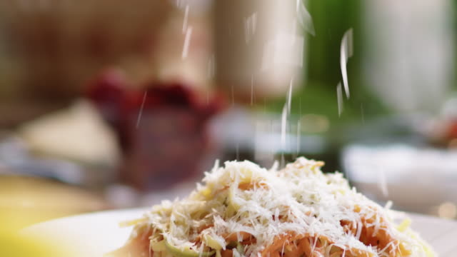 Grating Cheese over Cooked Spaghetti Close up view of hands of male cook in apron using handheld metal grater while grating cheese over cooked spaghetti pasta on plate while preparing dish in the kitchen spaghetti stock videos & royalty-free footage