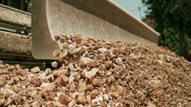 slo mo gravel being distributed across the construction site with a digger - ghiaia video stock e b–roll