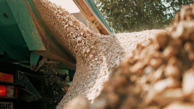 vídeos y material grabado en eventos de stock de slo mo grava siendo descargada en el sitio de edificio y caen fuera del camión - material de construcción