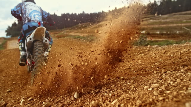 speed ramp gravel bursting around as motocross bike drives by - motocross video stock e b–roll