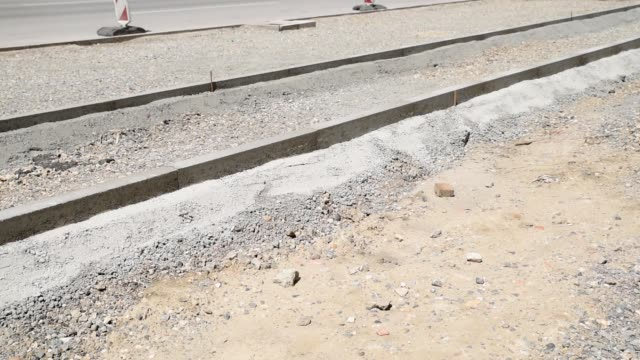 Gravel stone and sand with roadside or curb for new pedestrian walkway or sidewalk with bicycle lane at new street reparation and reconstruction construction site