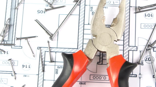 grigio e rosso pinze sul piano dell'edificio, piano delle unghie, rotazione, dall'alto - pinze attrezzo manuale video stock e b–roll