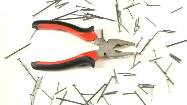 grigio e rosso pinze su bianco delle unghie, rotazione - pinze attrezzo manuale video stock e b–roll