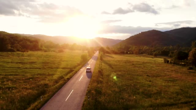 A gray car drives down an empty country road at a golden summer sunset