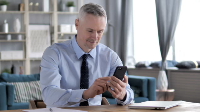 gray hair businessman using smartphone - capelli grigi video stock e b–roll