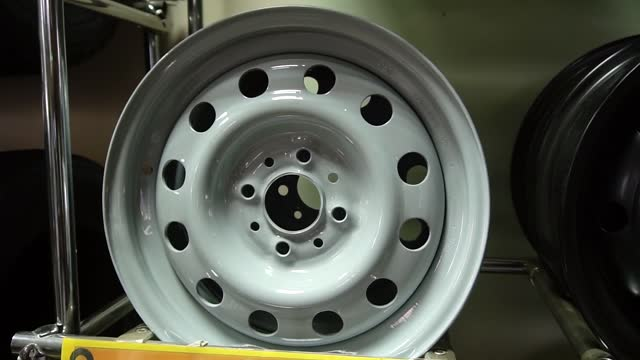 A gray new car rim sits on a shelf in an auto parts store.