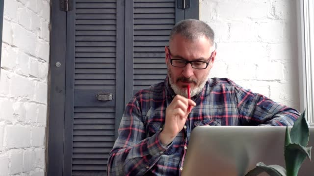 Gray-haired bearded male accountant working at home behind a laptop, making a report against the backdrop of a minimalist interior, studies information, considers, writes in a notebook, drinks tea or coffee.