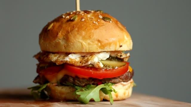 vídeos y material grabado en eventos de stock de gran hamburguesa de chuleta de ternera, tomates, setas y pepinos con queso fundido gira sobre una tabla de madera sobre fondo claro - hamburguesa