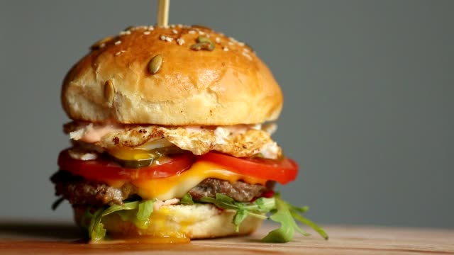 great burger with beef cutlet, tomatoes, mushrooms and cucumbers with melted cheese rotates on a wooden board on light background - burgers stock videos and b-roll footage