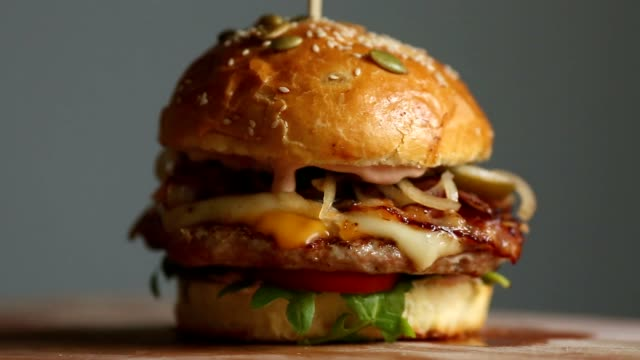 vídeos de stock e filmes b-roll de great burger with beef cutlet, tomatoes, mushrooms and cucumbers with melted cheese rotates on a wooden board on light background - hambúrguer comida