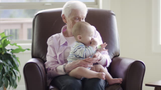 Great grandmother holding and playing with her great grandson video