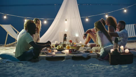 Great Summer Night Young friends sitting at the beach picnic at night, talking, laughing, toasting and drinking summer cocktails boho stock videos & royalty-free footage