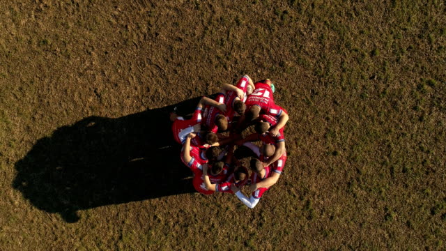 Great team spirit Young and strong rugby team on the field, holding hands all together, aerial view. rugby stock videos & royalty-free footage
