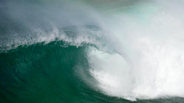 stockvideo's en b-roll-footage met grote turquoise gekleurde oceaan golf langzaam rollen het oppervlak van het water en het produceren van een veel wit schuim. 4k - reus fictief figuur