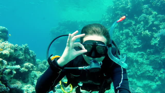 Great vacation and diving in the warm sea. The scuba diver signs the okay sign and takes himself off on a video of Self pin video