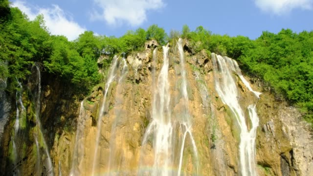 great waterfall (veliki slap) with rainbow at the bottom, in plitvice lakes national park, croatia, on a sunny morning - tilt down. 4k dci, 200 mbps. - национальный парк плитвицкие озёра стоковые видео и кадры b-roll