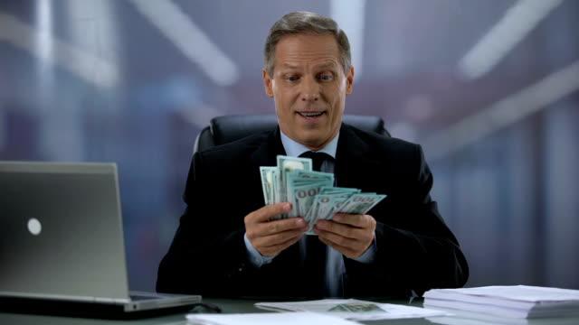 vídeos de stock e filmes b-roll de greedy businessman holding bunch of dollars, rejoicing easy income, high salary - abundância