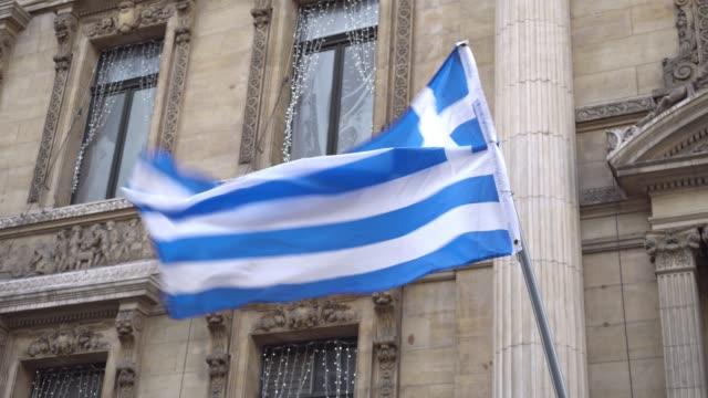 stockvideo's en b-roll-footage met griekse vlag zwaaien op de sterke wind op de achtergrond van gebouwen - athens