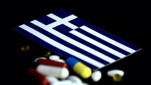 greek flag with lot of medical pills isolated on black background - grecia stato video stock e b–roll